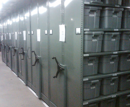 Police department evidence storage in bins on mobile shelving system 3, green end panel with chain guard cover